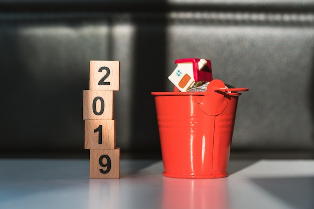 Wooden block year 2019 and miniature house in red bucket with stack coins