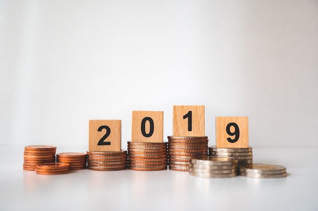 Wooden block year 2019 on stack coins using as business and financial concept