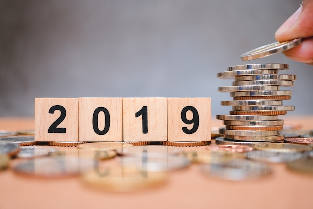 Wooden block year 2019 with hand holding stack coins using as business and financial concept