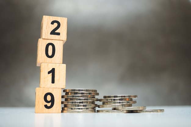 Wooden block year 2019 with stack coins using as business and financial concept