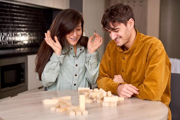 Деревянные блоки про осень, молодые люди играют в игру дома