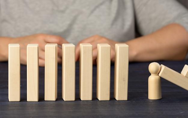 Деревянные блоки и фигурка человека останавливают падение