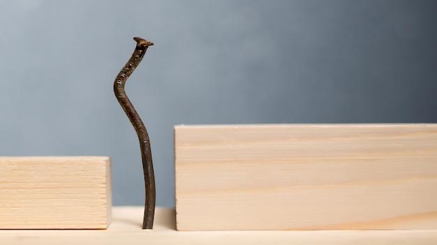 木製のブロックと曲がった釘。サラリーマンのしゃがみコンセプト。 -画像