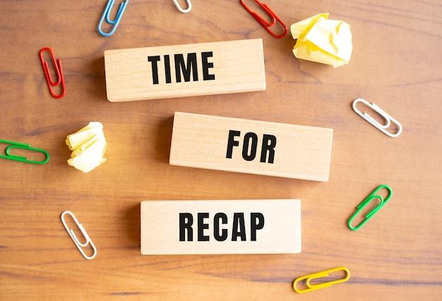 나무 블록이 테이블에 흩어져 있습니다. time for recap이 블록에 기록됩니다. 디자인에 대한 개념입니다.