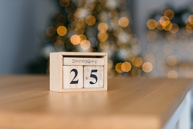 Wooden blocks calendar with the date of december 25 on the christmas lights. winter holidays mood.