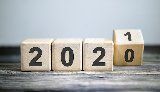 Wooden blocks for change year 2020 to 2021 . new year and holiday concept.