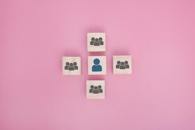 ピンクの背景で一緒に接続された木製のブロック。協力、チームワーク、ネットワーク、コミュニティのコンセプト。