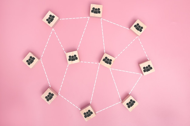 Wooden blocks connected together on pink background. cooperation, teamwork, network and community concept.