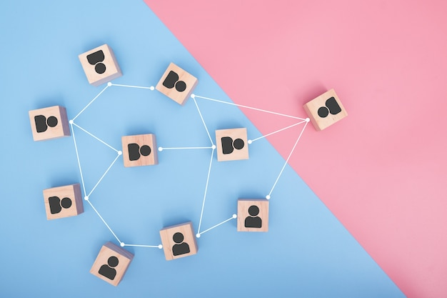 Wooden blocks connected together on pink and blue background. cooperation, teamwork, network and community concept.