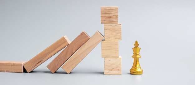 Wooden blocks or dominoes falling to golden chess king figure