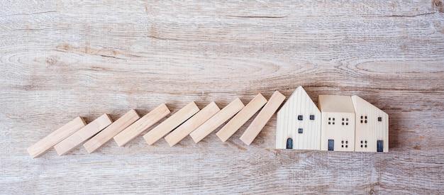 Wooden blocks falling house model on table background.