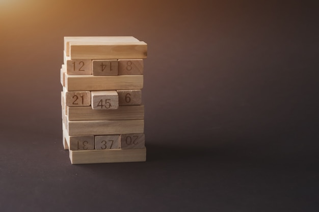 Wooden blocks folded into the tower with sunshine on brown background. success, growth