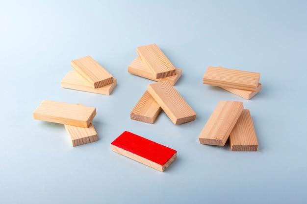 ペアの木製ブロックと愛のカップルとシングル、独身のシンボルとして1つの赤。多様性と個性と独自性。排除、孤独、違い、差別の概念。
