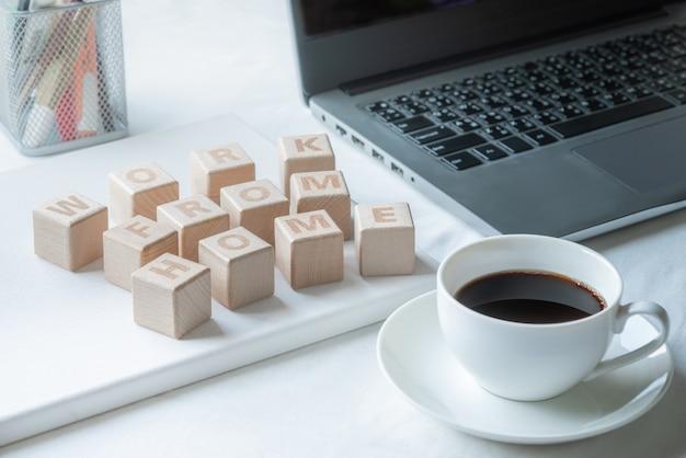 ラップトップコンピューターとコーヒーカップが付いている机の上の家からの単語の仕事の木製のブロック