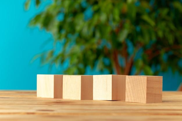 ぼやけた植物の背景、正面図に対して机の上の木製ブロック