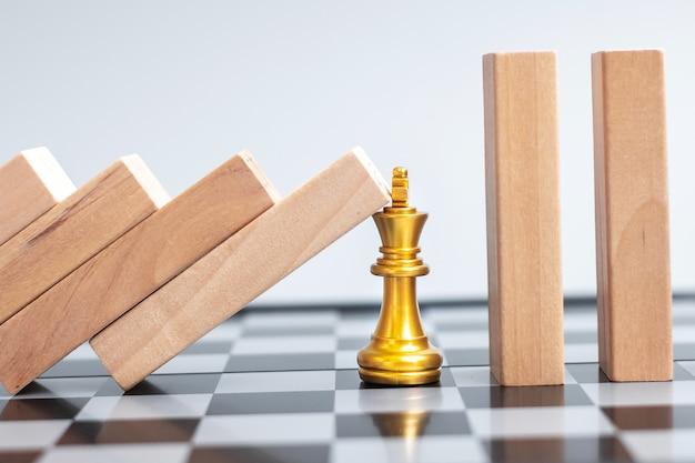 黄金のチェス王の姿に落ちる木製のブロックまたはドミノ。ビジネス、リスク管理、ソリューション、経済回帰、保険