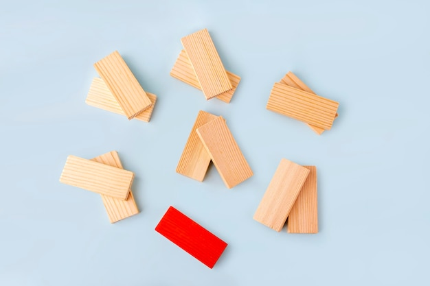 Wooden blocks in pairs and one red as symbol of love couple and single, bachelor. diversity and ndividuality and uniqueness. concept of exclusion, loneliness, difference, discrimination.