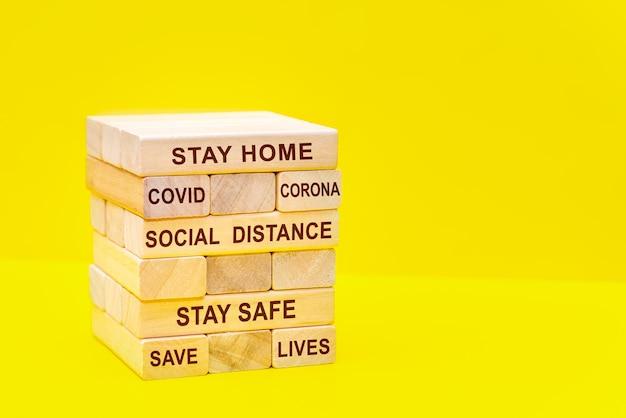 碑文の社会的な距離と黄色の背景にクローズアップで積み重ねられた木製のブロック