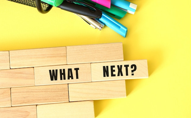 Wooden blocks stacked next to pens and pencils on a yellow background what next text on a wooden block