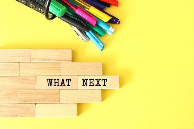 Wooden blocks stacked next to pens and pencils on a yellow background. what next text on a wooden block.