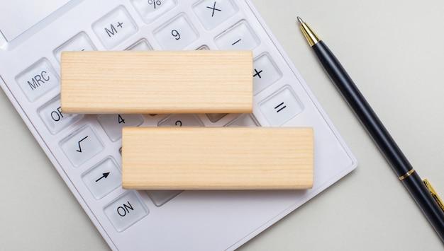 Деревянные блоки с местом для вставки текста лежат на светлом фоне на белом калькуляторе. рядом черная ручка. шаблон. бизнес-концепция