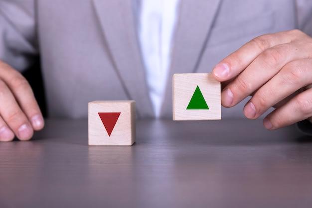 赤い下向き矢印と緑の上向き矢印の付いた木製のブロック。成功するビジネスと経済発展のプロセス。