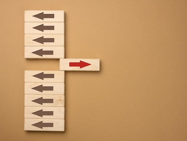 한 방향으로 갈색 화살표가있는 나무 블록과 반대 방향으로 빨간색 화살표가있는 한 블록. 다른 사람들과는 다른 차이의 개념, 사고의 독창성