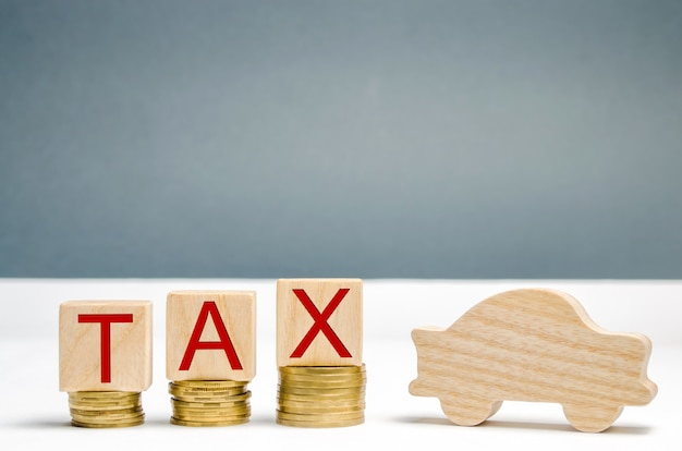 Wooden blocks with coins and the word tax and wooden auto. the concept of growth taxes on cars.