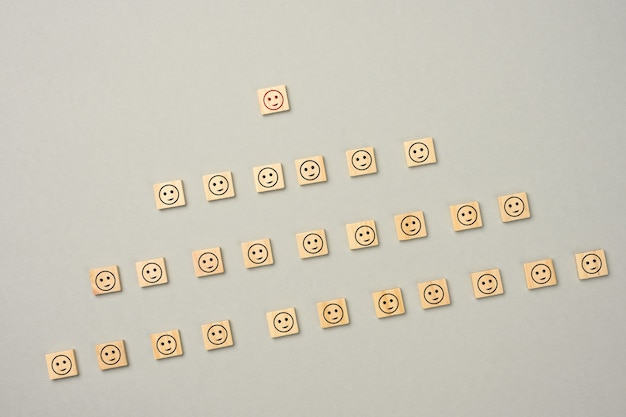 Wooden blocks with figures on a gray  surface, hierarchical organizational structure of management, effective management model in the organization,  top view Premium Photo