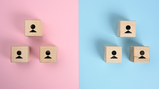 Wooden blocks with figures on a pink blue surface, hierarchical organizational structure of management, effective management model in the organization,  top view