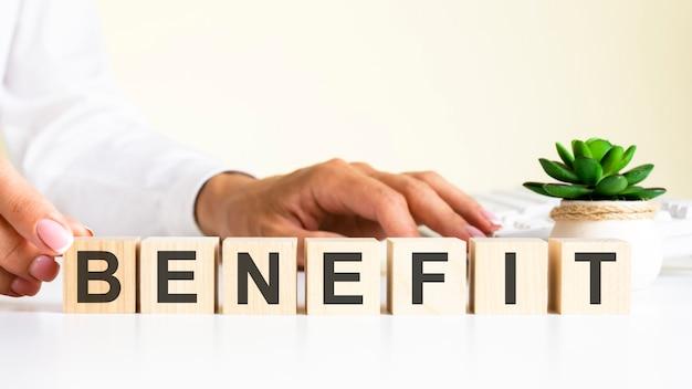 사무실 책상에 benefit라는 글자가 있는 나무 블록, 정보 및 통신 배경