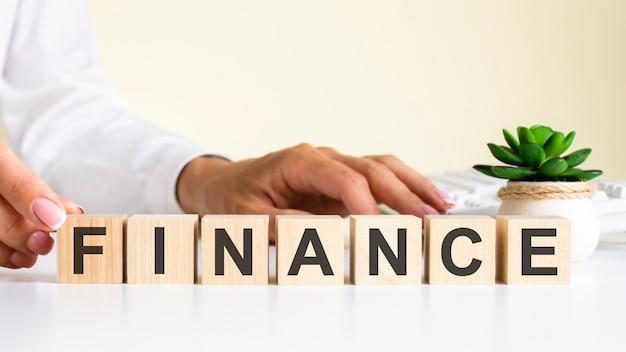 Деревянные блоки с буквами финансы на офисном столе, информационный и коммуникационный фон, выборочный фокус на офисном рабочем месте