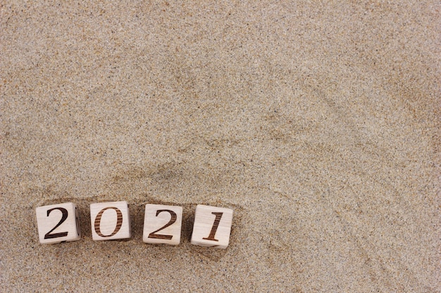 Wooden blocks with the numbers 2021 are located on the sand on the beach