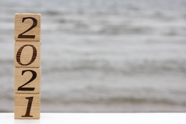Wooden blocks with the numbers 2021 are standing on the top of each other