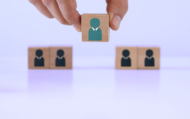 Wooden blocks with people icon on blue background, human resource management and recruitment concept