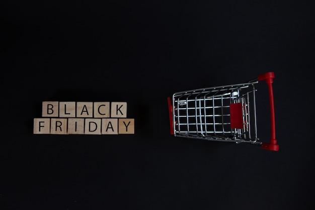 スーパーマーケットのカートの横にブラックフライデーの看板が付いた木製のブロック