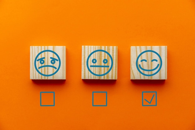 Деревянные блоки с символом счастливого лица улыбающегося лица на оранжевом фоне, оценка, повышение рейтинга, клиентский опыт, удовлетворенность и концепция рейтинга лучших отличных услуг