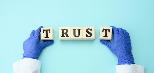 의사의 손에 대한 비문 신뢰, 의사 및 의료 시스템에 대한 신뢰가있는 나무 블록