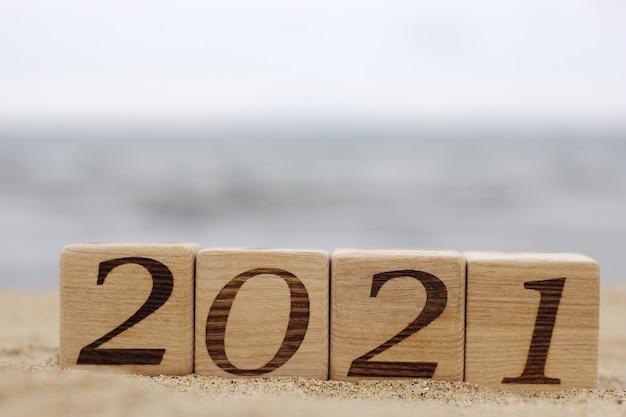 Деревянные блоки с номерами 2021 расположены на песке на пляже.