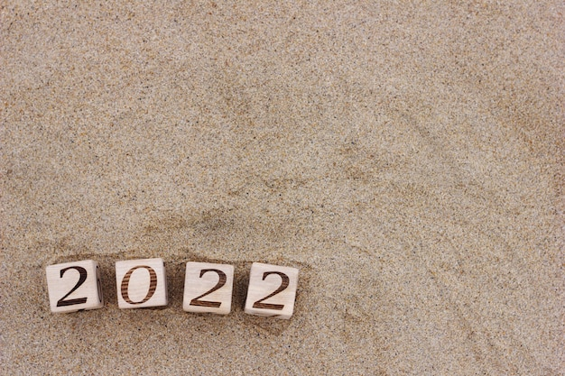 숫자 2022의 나무 블록은 해변의 모래 위에 있습니다.