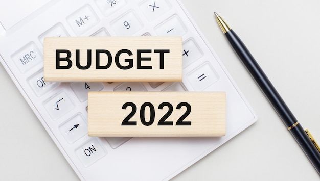 Деревянные блоки с текстом бюджет 2022 лежат на светлом фоне на белом калькуляторе. рядом черная ручка. бизнес-концепция