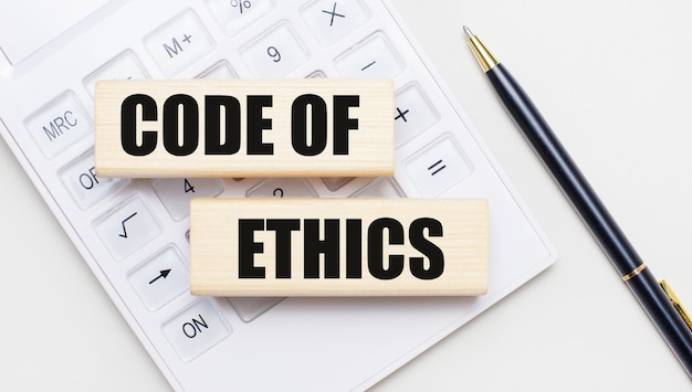 Code of ethicsというテキストが書かれた木製のブロックは、白い電卓の明るい背景にあります。近くには黒いハンドルがあります。ビジネスコンセプト