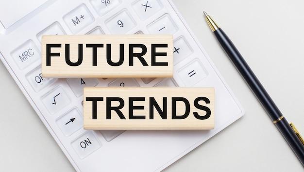Future trendsというテキストが付いた木製のブロックは、白い電卓の明るい背景にあります。近くには黒いハンドルがあります。ビジネスコンセプト