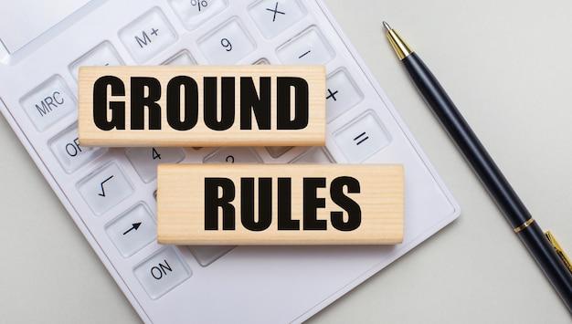 Деревянные блоки с текстом «правила земли» лежат на светлом фоне на белом калькуляторе. рядом черная ручка. бизнес-концепция