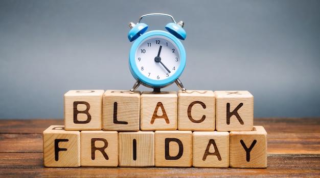 単語ブラックフライデーと時計の木製のブロック。販売と割引。低価格。