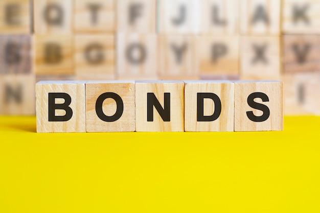 Деревянные блоки с надписью bonds. облигация - это ценная бумага, которая указывает на то, что инвестор предоставил ссуду эмитенту. эквивалентный заем. необеспеченные, обеспеченные облигации. бизнес и финансы