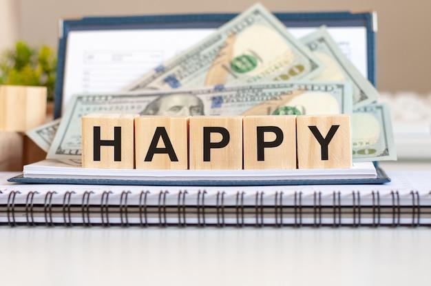 행복 한 단어로 나무 블록입니다. 나무 조각 및 달러 배경에 비즈니스 개념