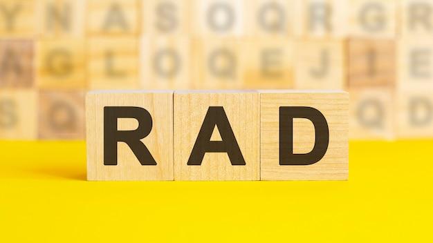 Деревянные блоки с надписью rad. эквивалентный заем. необеспеченные, обеспеченные облигации. бизнес и финансы. rad - сокращение от быстрой разработки приложений.