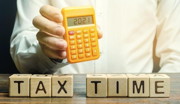 계산기에 비문 2021와 세금 시간 및 납세자 단어로 나무 블록.