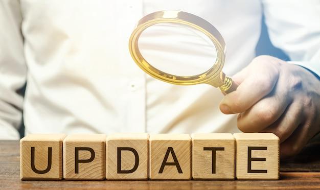 更新という言葉と虫眼鏡が付いた木製のブロック。バージョンの更新